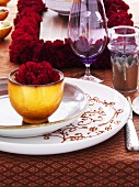Festive place-setting with red carnation