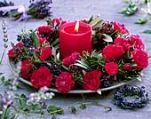 Kranz aus roten Rosen und Kräutern um rote Kerze