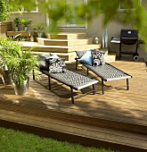 Two loungers and barbecue on decking