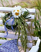Small wreath of grasses and oxeye daisies on chair back