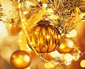 Goldfarbene Weihnachtskugel hängt am Baum