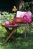 Garden table and pink garden chair with cushion and bag