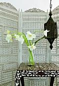 Tisch mit Blumen, Lampe und Raumteiler im marokkanischen Stil