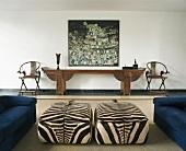 Wohnzimmer mit Polsterhockern im Zebra-Look, länglichem Konsolentisch & modernem Wandgemälde