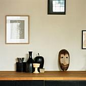 Afrikanische Maske und Vasen auf einem Sideboard
