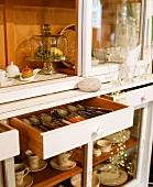 A crockery cupboard with cutlery drawers