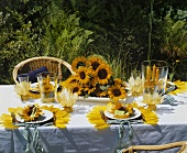 A festively laid table decorated with sunflowers in the garden