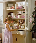 A girl standing in front of a crockery cupboard