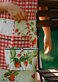 A girl wearing and apron and carring a bag with a strawberry pattern