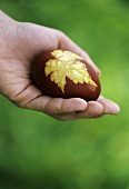 A decorated Easter egg with a leaf motif in someone's hand