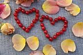 Zwei Herzen aus Beeren, umgeben von Rosenblättern
