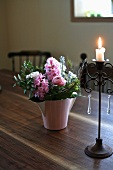 A bunch of flowers and a candle on a wooden table