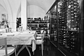 A black and white photo of a designer restaurant with a vaulted ceiling and wine racks