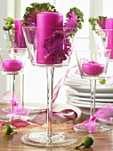 Pink candles and ornamental cabbage leaves in glasses