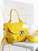 Yellow handbag and lemons on a chair