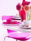 Table laid in pink with coffee and sandwich cookies
