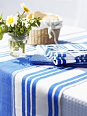 Table laid in blue & white with marguerites & bread basket