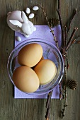 Three eggs in a glass dish with porcelain rabbit