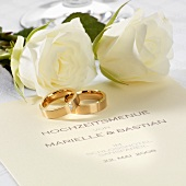 Wedding menu, wedding rings and white roses