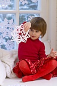 Girl playing with snowflake decoration