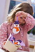 Girl holding salt dough snowman (tree ornament)