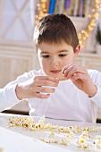 Boy threading popcorn (to make popcorn wreath)