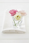 Three lisianthus flowers in a glass
