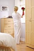 Woman in pyjamas putting vase of flowers on bedroom window sill