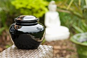 A black jar with lid in an oriental garden, Burma