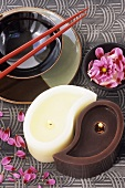 Candles forming yin-yang symbol and Asian place-setting