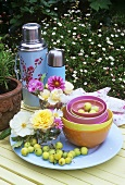 Flowers, bowls and Thermos flasks on table out of doors