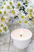 Eine Kerze und Asterblüten
