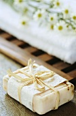 A bar of soap and towel with white asters