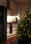 Decorated Christmas tree near a kitchen