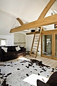 Attic sitting room with couch, cowhide rug, wooden beam