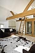 Wohnzimmer im Dachgeschoss mit Balkendecke, Couch, Kuhfell & Holzleiter zu kleiner Galerie