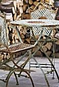 Alte Eisenstühle mit Tischchen vor einem Holzhaufen