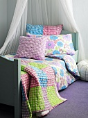 Bed with canopy, bedspread and cushions