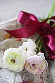 Bunch of ranunculus with red bow