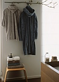 Two dressing gowns hanging on wall above stacked towels on stool
