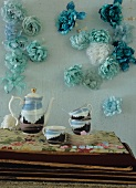 Painted coffee service in front of turquoise wall with fabric flowers