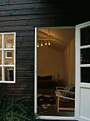 Blick durch geöffnete Tür eines Holzhauses in beleuchtetes Schlafzimmer mit Bett & Kuhfell