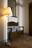 Floor lamp with lampshade and antique bench on tiled floor