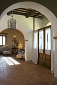 Foyer in a country home with brick arches with a view to an living room (open floor plan)