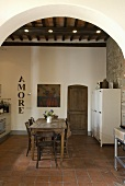 View through arches onto a dining area and tile floor of a Mediterranean country home