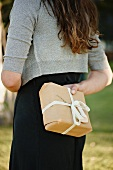 A woman holding a parcel behind her back