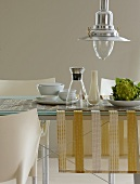 A dining table with a table runner, a carafe, a vase and Romanesco broccoli