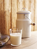 A glass of a milk and a milk churn