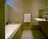 An elegant designer bathroom with light brown floor and wall tiles