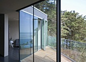 A modern house with a view through an open terrace door onto a terrace with wooden boards and a glass balustrade